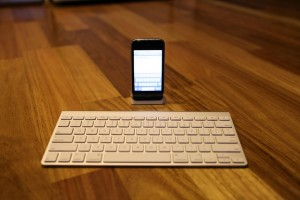 iPhone with apple wireless keyboard at desk